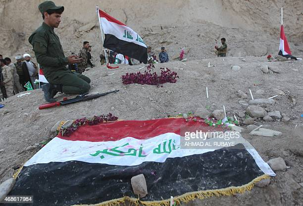 An Iraqi Shiite fighter and member of Iraq's Popular Mobilisation prays at a burial site believed to hold victims of a June massacre in which...