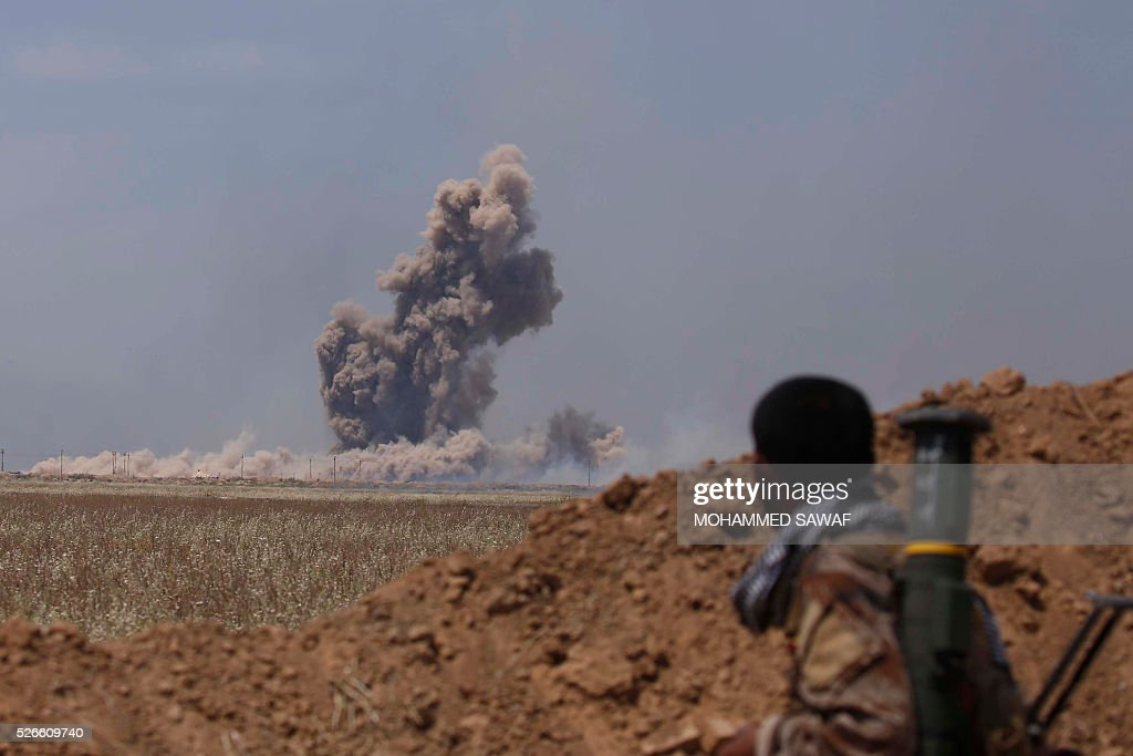 An Iraqi Shiite fighter from the Furqat al-Abbas brigades looks towards smoke billowing during an operation to retake the town of al-Bashir, near Kirkuk, from the Islamic State group (IS), on April 30, 2016. Iraqi forces launched a final assault Saturday to retake the Turkmen majority town of Bashir from the Islamic State jihadist group, Kurdish authorities said. 'Bashir village is surrounded and 80 percent has been cleared,' the Kurdistan Region Security Council said on social media. Turkmen units from Iraq's Hashed al-Shaabi (Popular Mobilisation) militia umbrella group, which announced an operation to retake the town earlier this month, were also taking part. / AFP / Mohammed SAWAF