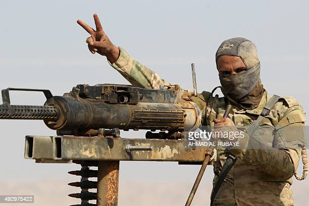An Iraqi Shiite fighter from the Popular Mobilisation units fighting alongside Iraqi forces flashes the vsign for victory in the town of Baiji north...