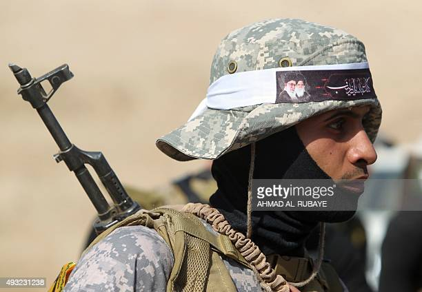 An Iraqi Shiite fighter from the Popular Mobilisation units fighting alongside Iraqi forces stands wearing an Islamic headband bearing portraits of...