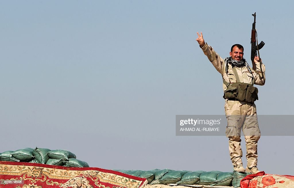 An Iraqi Shiite fighter from the Popular Mobilisation units, flashes the sign for victory while he monitors the frontline near the Tharthar lake, north of the city of Fallujah on February 11, 2016, as they continue to battle Islamic State group (IS) jihadists. RUBAYE