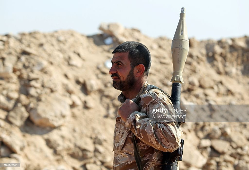 An Iraqi Shiite fighter from the Popular Mobilisation units, monitors the frontline near the Tharthar lake, north of the city of Fallujah on February 11, 2016, as they continue to battle Islamic State group (IS) jihadists. RUBAYE