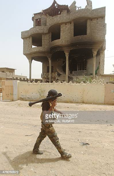 An Iraqi Shiite fighter from the Popular Mobilisation units walks with a rocket launcher in the town of Baiji north of Tikrit as they fight alongside...