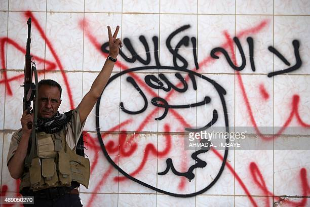 An Iraqi Shiite fighter from the Popular Mobilization units flashes the sign for victory in front of defaced Islamist graffiti in the northern city...