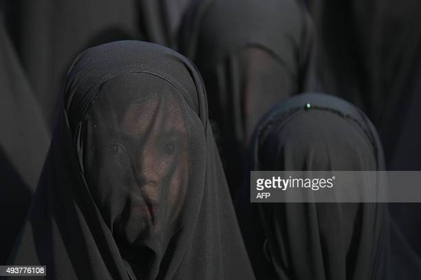 An Iraqi Shiite girl whose face is covered with a veil takes part in a parade in preparation for the peak of the mourning period of Ashura in...