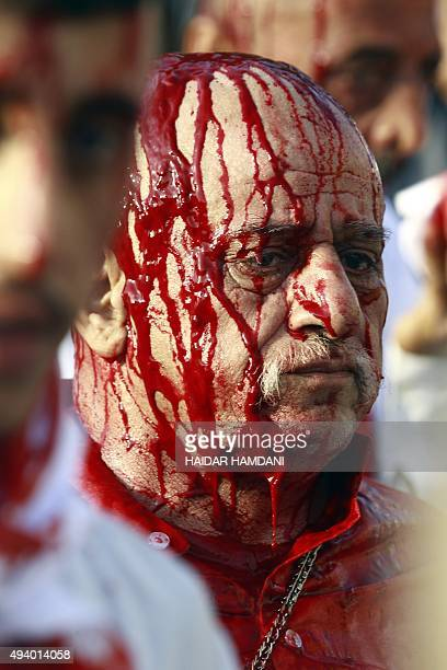 An Iraqi Shiite man has his face covered with blood as he takes part in the Ashura religious ritual during which participants cut their scalps with...