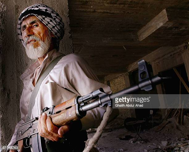 An Iraqi Shiite man loyal to the radical Shiite cleric Moqtada alSadr holds his AK 47 during the fighting on August 6 2004 in Najaf Iraq Mahdi Army...