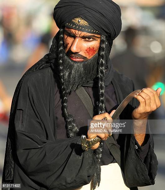 An Iraqi Shiite man performs during the reenactment of the Battle of Karbala as part of a parade in preparation for the peak of the mourning period...