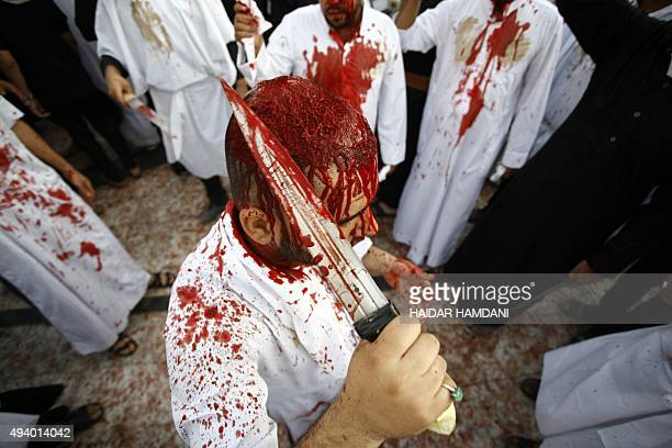 An Iraqi Shiite man takes part in the Ashura religious ritual during which participants cut their scalps with machetes on October 24 2015 in the holy...