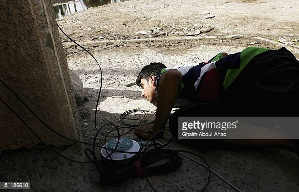 An Iraqi Shiite militia man loyal to the radical cleric Moqtada alSadr watches for US tanks from behind a wall with an IED detonator in his hand...