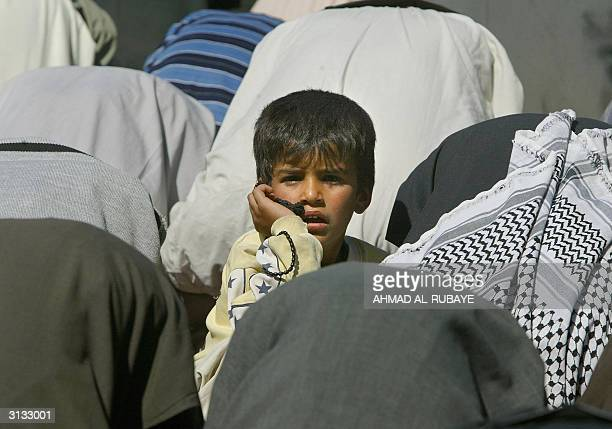 An Iraqi Shiite Muslim boy sits amid hundreds of worshippers during the weekly Friday prayer 26 March 2004 in the holy city of Karbala 100 kms south...