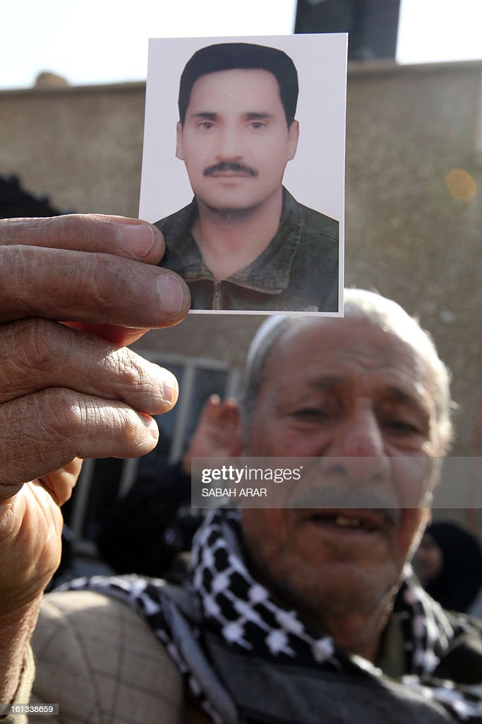An Iraqi Shiite Muslim man holds a photo of a relative during a rally in the capital Baghdad on February 10, 2013, protesting against a call to abolish the de-Baathification law which bans senior members of the regime of former Iraqi president Saddam Hussein from government employment, the modifications to the anti-terrorism laws and an amnesty for Sunni prisoners convicted on terrorism charges, brought into effect following the fall of Saddam Hussein in April 2013. The rally follows weeks of protests by the Sunnis hoping that through their protests and sit-ins that have swept across Sunni provinces and Baghdad's Sunni neighbourhoods they can abolish the political structure forged by the US occupation authority, allowing them to negotiate a more equitable governing system. AFP PHOTO / SABAH ARAR