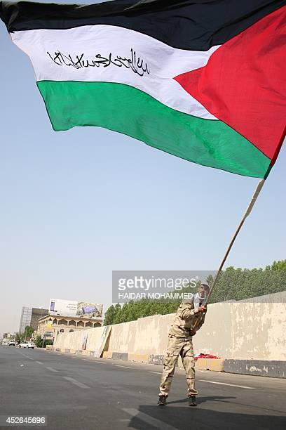 An Iraqi Shiite Muslim militant holds up a Palestinian flag with Islamic calligraphy on it during a parade marking AlQuds International Day on July...