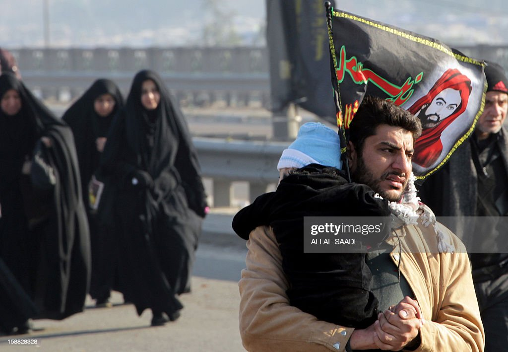 An Iraqi Shiite Muslim pilgrim (R) carries his child as he marches along the main highway that links the Iraqi capital Baghdad with the central shrine city of Karbala on December 31, 2012, to take part in the Arbaeen religious festival which mraks the 40th day after Ashura commemorating the seventh century killing of Prophet Mohammed's grandson, Imam Hussein. A series of bombings across Iraq killed at least 12 people on the sidelines of upcoming major commemoration ceremonies, including three policemen, and wounded more than 40, officials said.