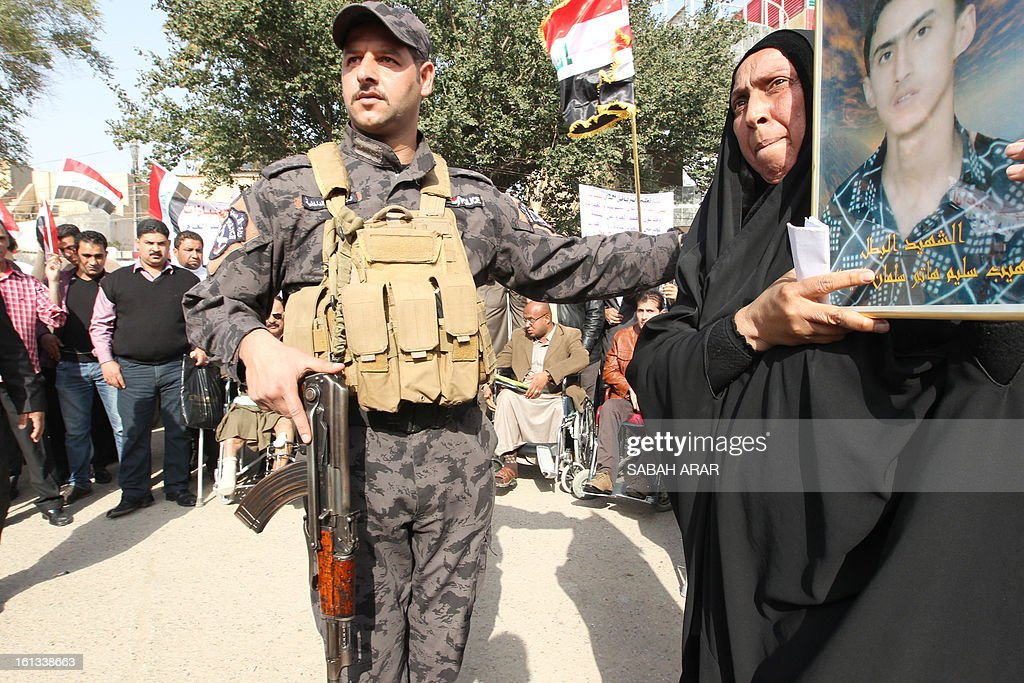 An Iraqi Shiite Muslim woman holds a photo of a relative during a rally in the capital Baghdad on February 10, 2013, protesting against a call to abolish the de-Baathification law which bans senior members of the regime of former Iraqi president Saddam Hussein from government employment, the modifications to the anti-terrorism laws and an amnesty for Sunni prisoners convicted on terrorism charges, brought into effect following the fall of Saddam Hussein in April 2013. The rally follows weeks of protests by the Sunnis hoping that through their protests and sit-ins that have swept across Sunni provinces and Baghdad's Sunni neighbourhoods they can abolish the political structure forged by the US occupation authority, allowing them to negotiate a more equitable governing system.