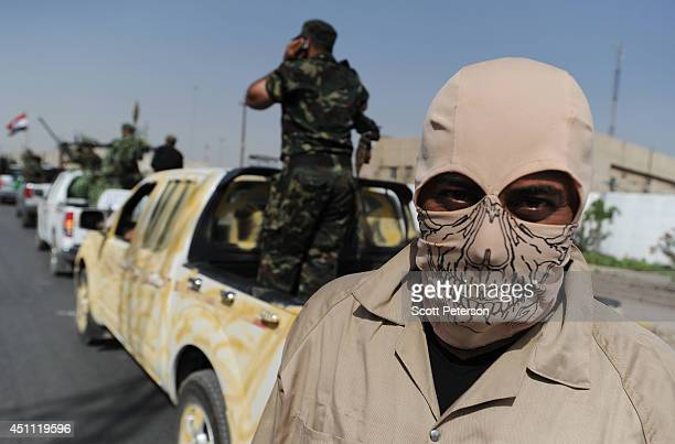 An Iraqi Shiite of the Mahdi Army militia loyal to cleric Moqtada alSadr wearing a skull face mask vows to fight ISIS in a show of strength in a...
