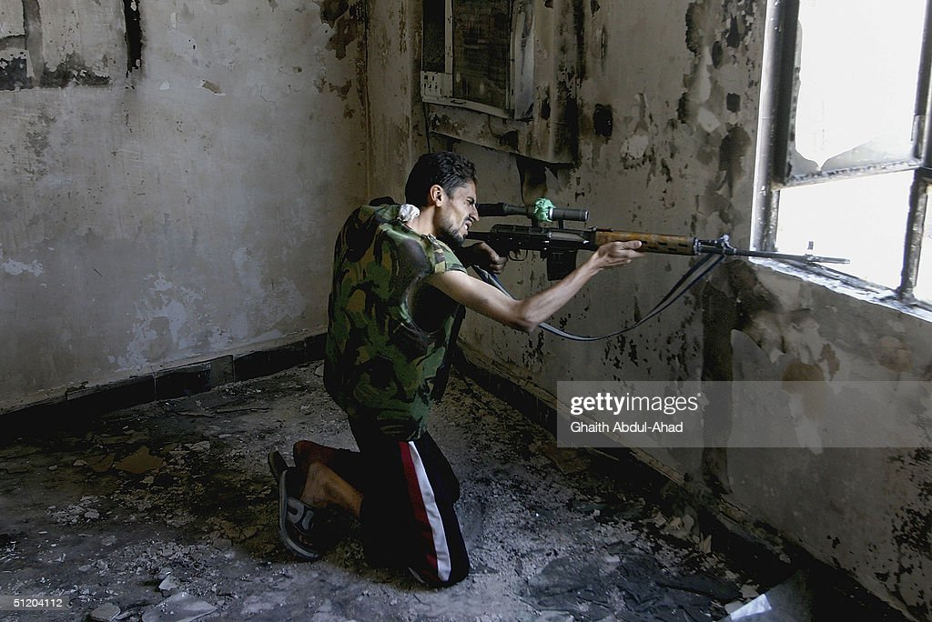 An Iraqi Shiite sniper loyal to the radical cleric Moqtada al-Sadr fires at US troops from an empty building on the outskirts of the Najaf cemetery, on August 22, 2004 in Najaf Iraq. After a night of heavy U.S. aerial bombardment the 18 day standoff around the Imam Ali Shrine continues with over 1000 Sadr supporters believed to be inside the building. (Photo by Ghaith Abdul-Ahad/Getty Images) .