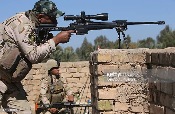 An Iraqi sniper takes position during fighting against jihadists from Islamic State group in the Garma district west of the Iraqi capital Baghdad in...