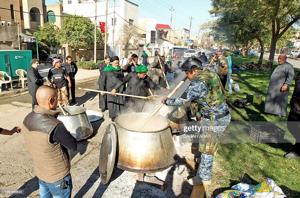 An Iraqi soldier and civilians stir pots of food on December 28, 2012, in the Karrada neighbourhood of Baghdad. The food is to be distributed to Iraqi Shiite Muslim pilgrims walking along the main highway linking the Iraqi capital to the central shrine city of Karbala where they will mark, later this week, the Arbaeen religious festival which is the 40th day after Ashura, commemorating the killing of Prophet Mohammed's grandson, Imam Hussein in the seventh century.