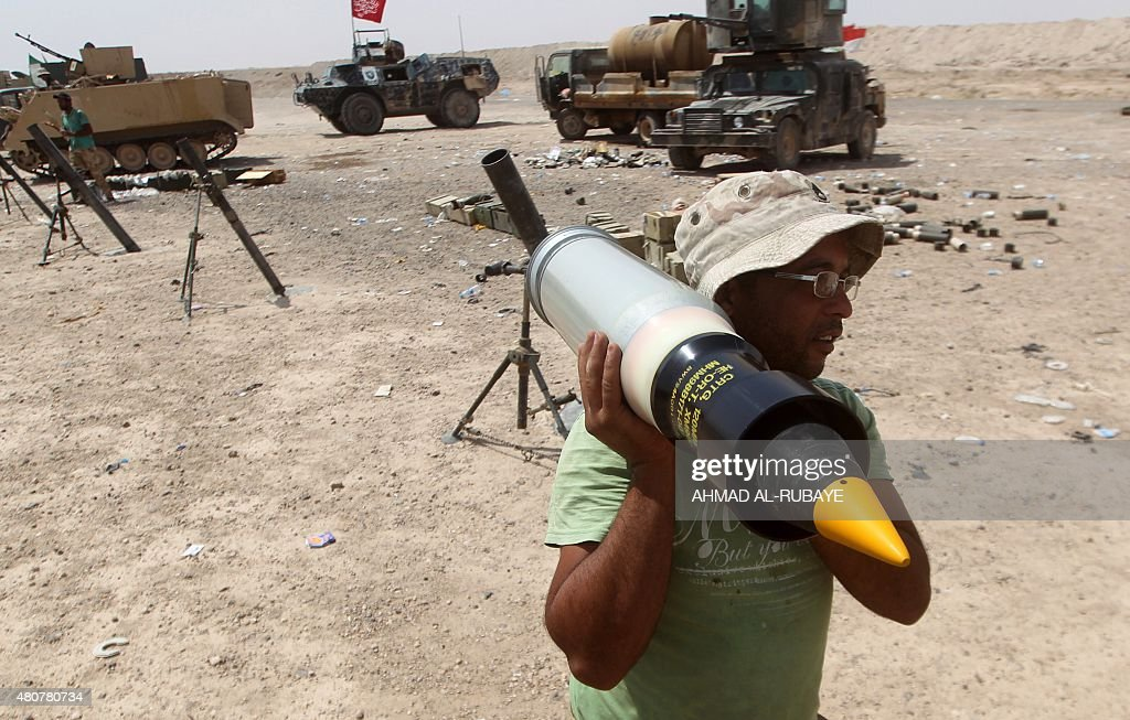 An Iraqi soldier carries a shell as forces supporting the government guard a position on July 15 2015 on the northern outskirts of the city of...
