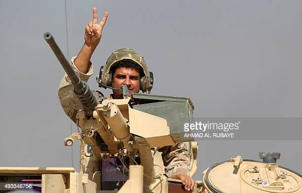 An Iraqi soldier fighting alongside Iraqi government forces and Shiite fighters from the Popular Mobilisation units displays the vsign for victory...