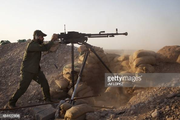 An Iraqi soldier fires a machine gun towards Islamic State positions during heavy clashes in Tuz Khurmatu in Salaheddin province about 88 kilometres...