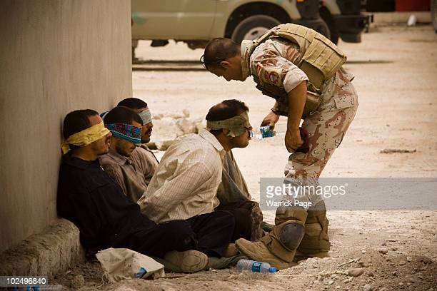 An Iraqi soldier from 2nd Division gives water to detainees after returning to their base from a morning mission on June 5 2010 in Mosul Iraq Iraq...