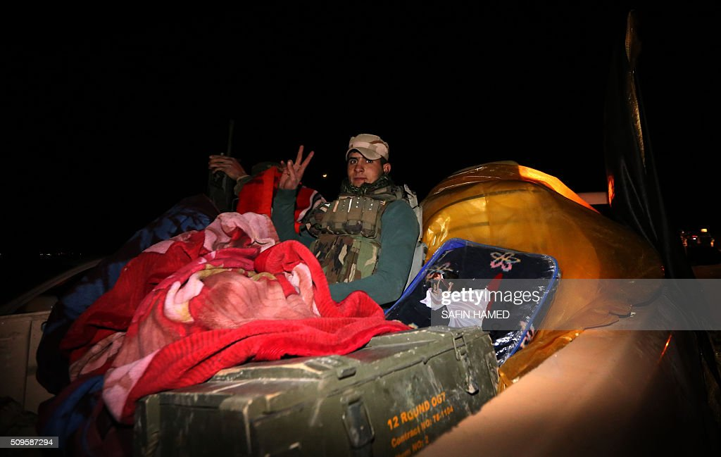 An Iraqi army member gestures to the camera as he sleeps on the back of an armoured vehicle headed towards Makhmur, about 280 kilometres (175 miles) north of the capital Baghdad, on February 11, 2016. The Iraqi army is deploying thousands of soldiers to a northern base in preparation for operations to retake the Islamic State (IS) group's hub of Mosul, according to officials, as IS still holds Fallujah, east of Ramadi, and Mosul, Iraq's second city that is located in the north. / AFP / SAFIN HAMED