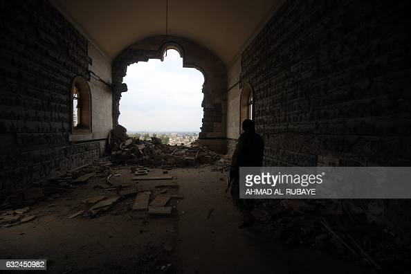 TOPSHOT An Iraqi soldier inspects the debris on January 22 2017 at St George's Monastery a historical Chaldean Catholic church on the northern...