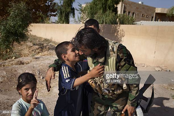 An Iraqi soldier kisses a child in Amerli on September 1 2014 after Iraqi forces broke through to the jihadistbesieged Shiite town the previous day...