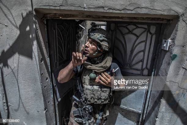 An Iraqi soldier quiets shouting civilians for fear they will attract Islamic State snipers in alNuri mosque complex of Mosul Iraq on June 29 2017...