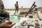An Iraqi soldier shows off a flyer for the 'The Islamic State of Iraq' which highlights senior alQaeda members as weapons seized by Iraqi security...
