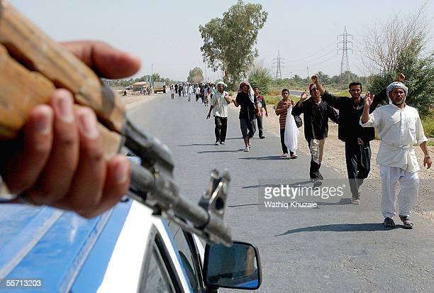 An Iraqi soldier stands guard as Shiite pilgrims walk towards the holy Shiite city of Karbala September 18 2005 which is located approximately 70...