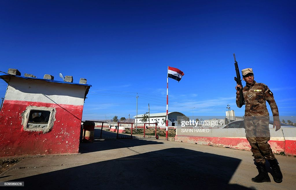 An Iraqi army member stands guard at the entrance of the Nineveh base for liberation operations in Makhmur, about 280 kilometres (175 miles) north of the capital Baghdad, on February 11, 2016. The Iraqi army is deploying thousands of soldiers to a northern base in preparation for operations to retake the Islamic State (IS) group's hub of Mosul, according to officials, as IS still holds Fallujah, east of Ramadi, and Mosul, Iraq's second city that is located in the north. / AFP / SAFIN HAMED