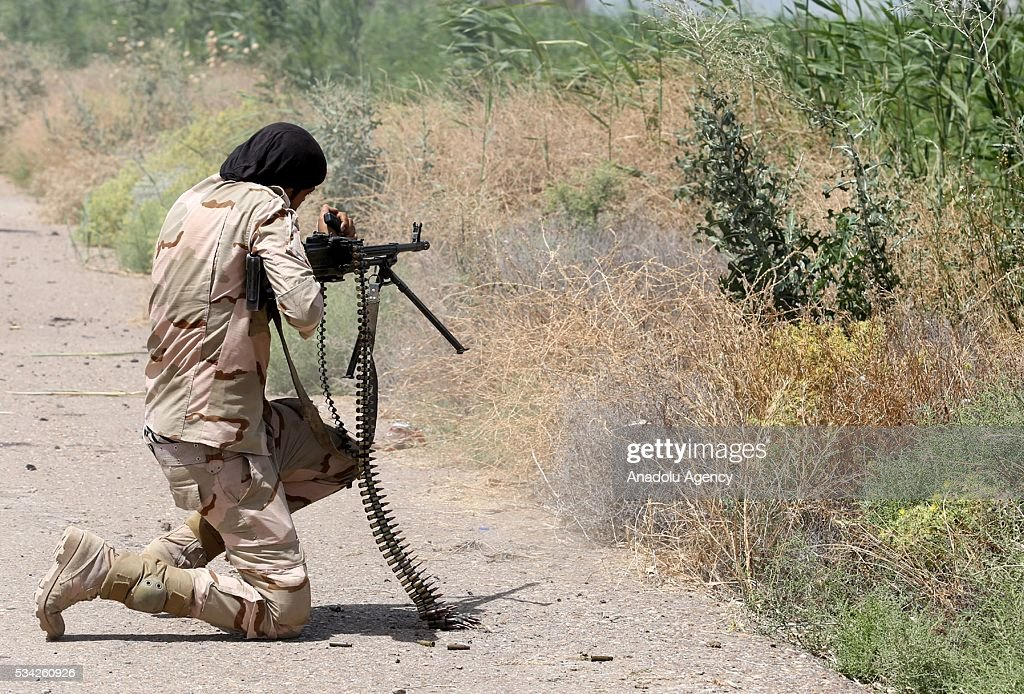 An iraqi soldier stands with his machine gun on the road between Felluce and Garma towns as they carry operations to rescue Felluce town from Daesh terrorists in Anbar, Iraq on May 25, 2016.