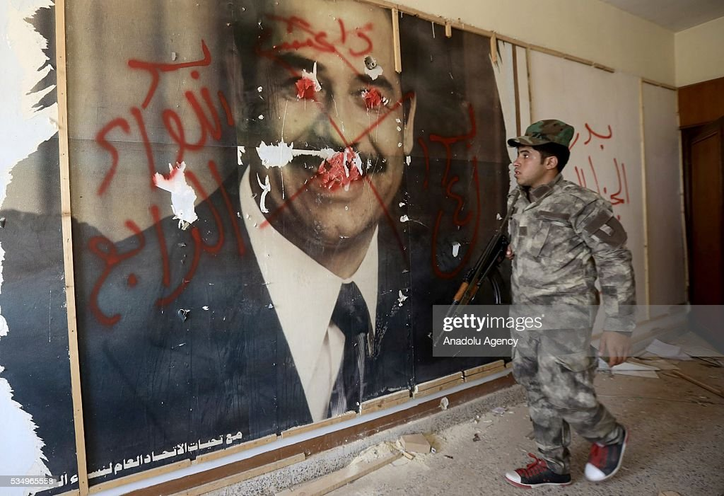 An Iraqi soldier stares at former Iraqi leader Saddam Hussein's poster during an operation to regain the city from Daesh terrorists inside the tunnels, dug by Daesh terrorist, in Fellujah, Iraq on May 28, 2016.