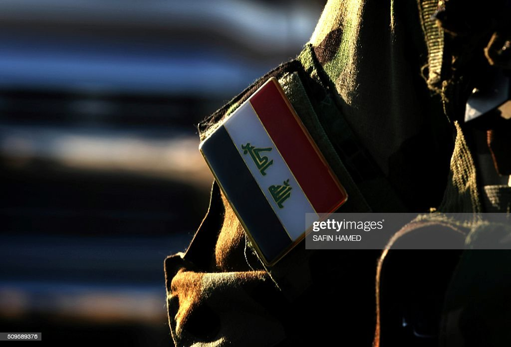 An Iraqi army member's badge is seen as he stands guard at the entrance of the Nineveh base for liberation operations in Makhmur, about 280 kilometres (175 miles) north of the capital Baghdad, on February 11, 2016. The Iraqi army is deploying thousands of soldiers to a northern base in preparation for operations to retake the Islamic State (IS) group's hub of Mosul, according to officials, as IS still holds Fallujah, east of Ramadi, and Mosul, Iraq's second city that is located in the north. / AFP / SAFIN HAMED