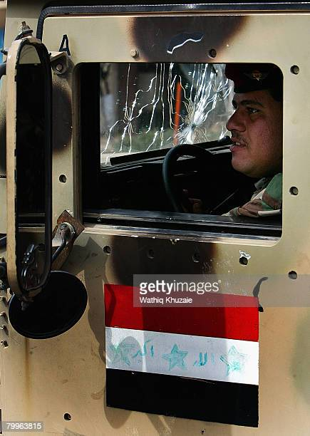 An Iraqi solider on street patrol loks on while Iraqi Shiite pilgrims march to the holy Shiite city of Karbala on February 24 2008 in Baghdad Iraq...
