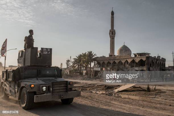 An Iraqi Special Operations Forces humvee passes a destroyed mosque in the liberated district of Al Jazaer eastern Mosul recently recaptured from...