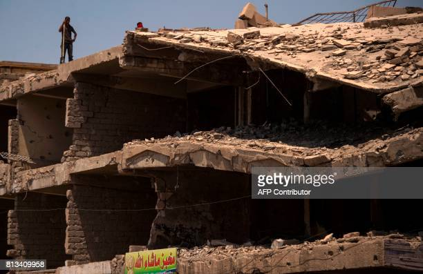 An Iraqi stands on top of a damaged building in west Mosul on July 12 2017 a few days after the government's announcement of the 'liberation' of the...