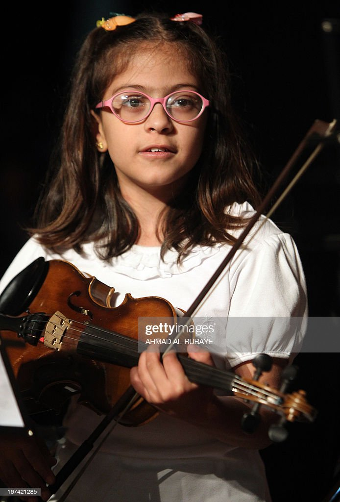 An Iraqi student from the ballet and music school, holds her violin as she performs during their annual production that marks the end of the school year, at al-Ribat hall theatre in central Baghdad on April 25, 2013.