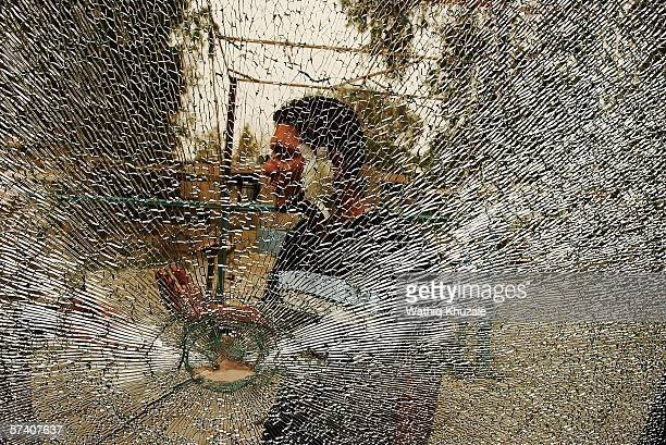 An Iraqi student is seen through a shattered glass at the scene of two car bomb explosions outside the Mustansiriya University on April 24 2006 in...