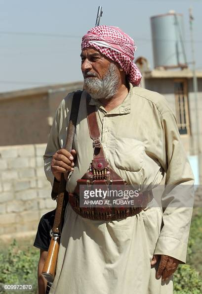 An Iraqi Sunni fighter from the popular mobilisation units supporting the government forces stands guard in the town of Sharqat around 80 kilometres...