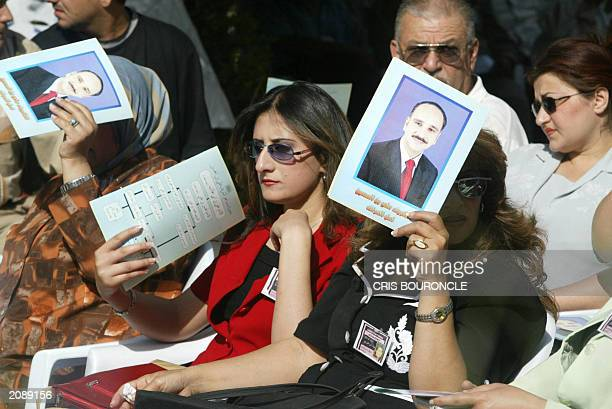 An Iraqi sympathizer to the Constitutional Monarchy Movement fans herself with a pamphlet emblazoned with the portrait of AlShareef Ali bin alHussein...