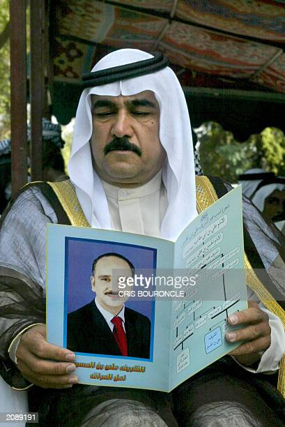An Iraqi sympathizer to the Constitutional Monarchy Movement reads a pamphlet emblazoned with the portrait of AlShareef Ali bin alHussein a pretender...