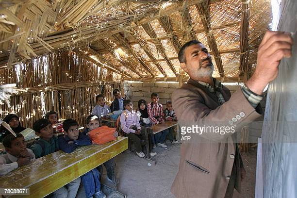 An Iraqi teacher lectures a class at a reedroofed school in the marshes area near the southern city of Nasiriyah 25 November 2007 Iraq's marshes were...