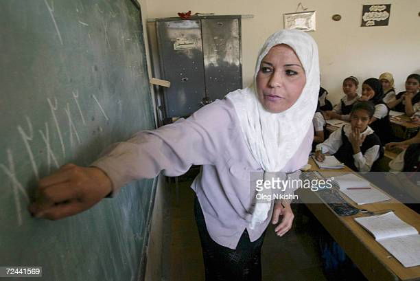 An Iraqi teacher teaches to school girls during a lesson in their classroom May 10 2003 in Baghdad Iraq One month after the collapse of Saddam...