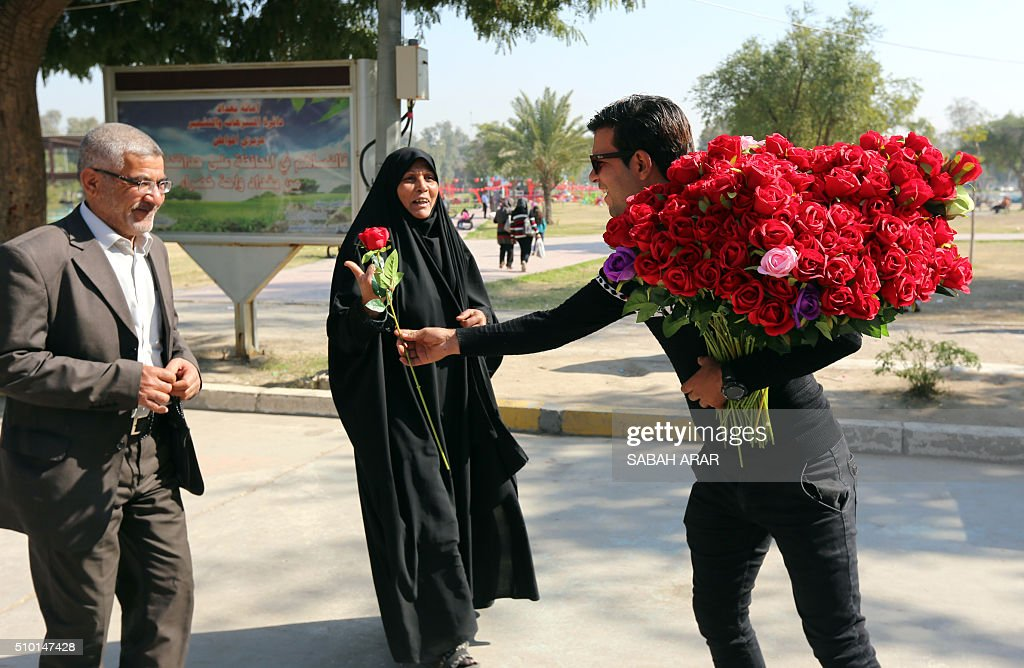 An Iraqi vendor offers flowers to a couple on Valentine's day at Baghdad's Al-Zawraa Park, on February 14, 2016. / AFP / Sabah ARAR