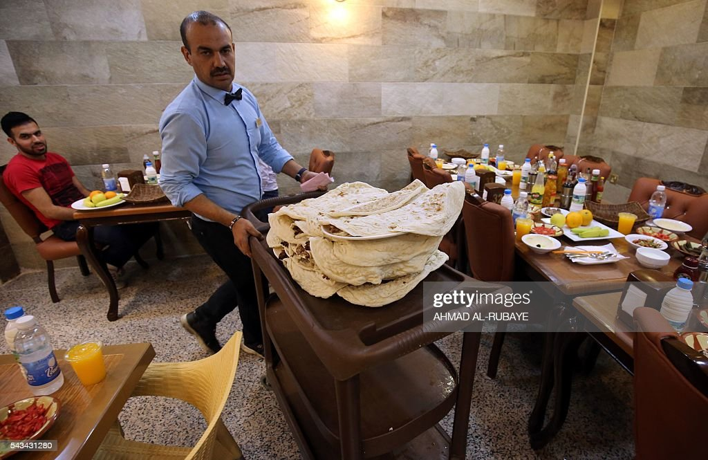 An Iraqi waiter works at a restaurant where customers come to break the fast with an Iftar diner during the Muslim feating month of ramadan on June 28, 2016 in the capital Baghdad. / AFP / AHMAD