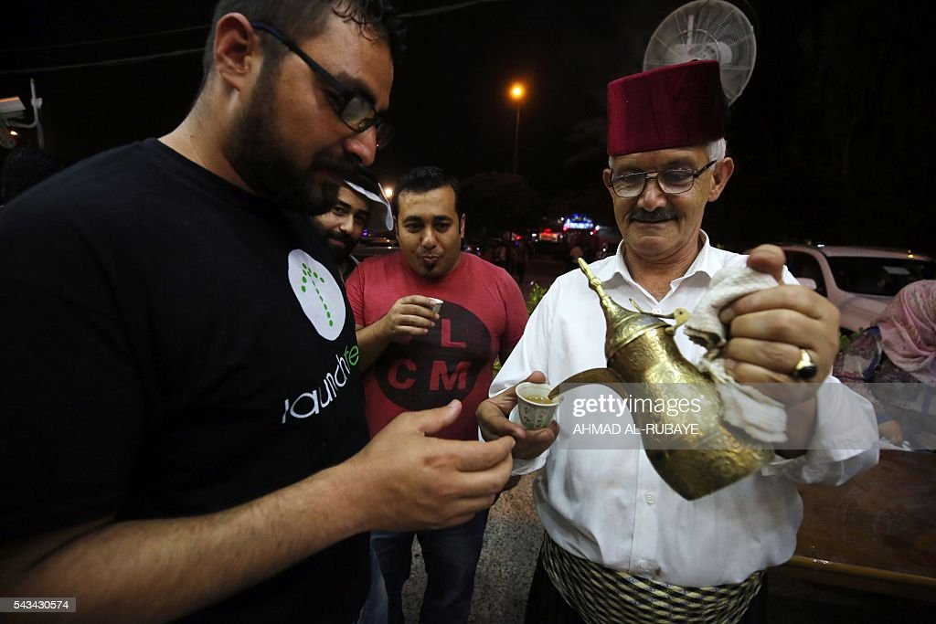 An Iraqi waiter serves traditional Arabic coffee to a customer at a restaurant where Muslim worshippers come to break the fast with an Iftar diner during the Muslim feating month of ramadan on June 28, 2016 in the capital Baghdad. / AFP / AHMAD